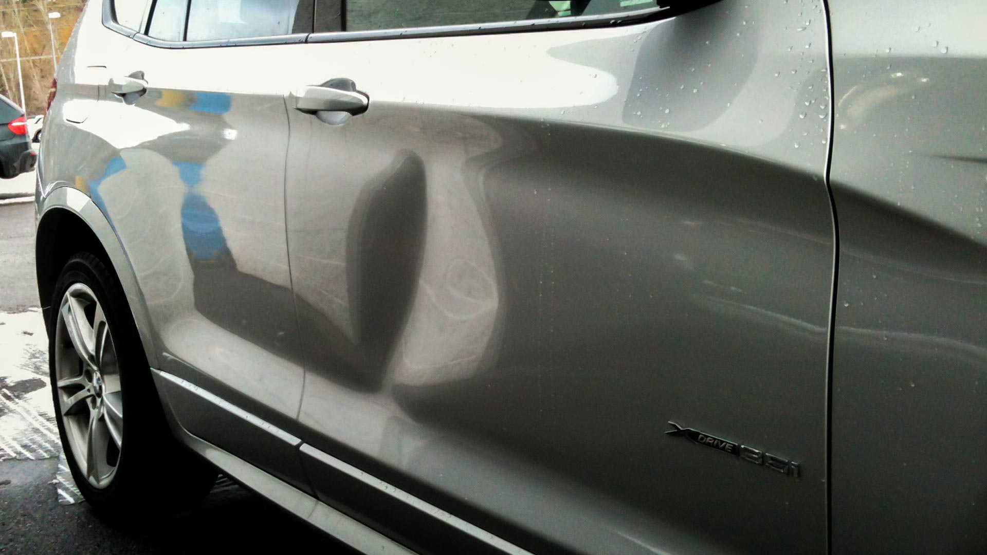 & 2013 BMW X3 dent in door panel - Dentique Paintless Dent Repair